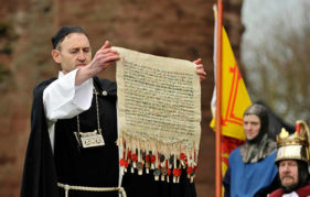 A replica of The Declaration of Arbroath is held aloft during the recreation of the signing of the historic document at the Tartan Day Scotland Festival