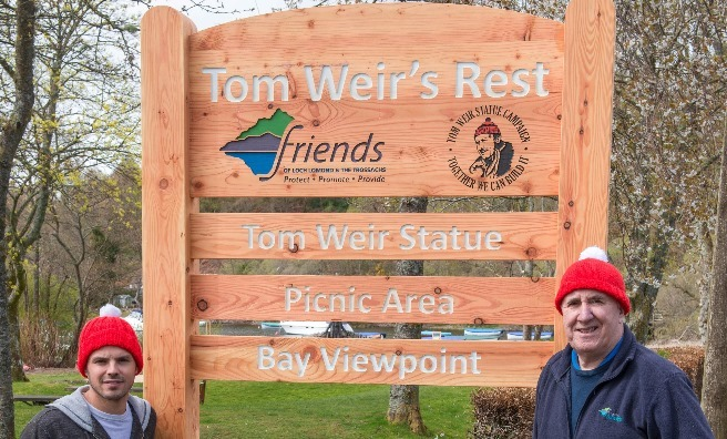 Stuart Fraser of the Oak Tree Inn and James Fraser, chair of the Friends of Loch Lomond & The Trossachs next to the Tom Weir's Rest sign