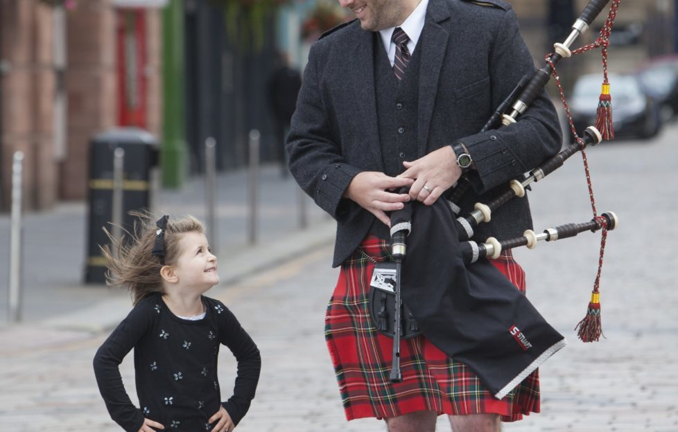 Andrew Douglas (29) from the Stuart Highlander Pipe Band give Grace Carruthers, 5, a lesson in piping last year