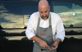 Monachyle Mhor's renowned chef, Tom Lewis, prepares oysters on the banks of a loch in Galloway Forest