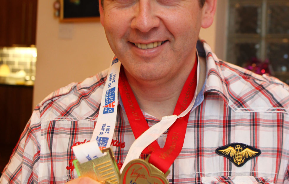 Bryn with his marathon medals - he says running helps the disease.